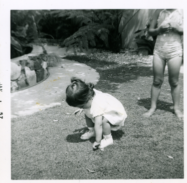 7. 1957-01 toddler michaela in the backyard with kathie