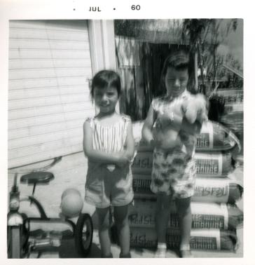 25. 1960-07 michaela & kathie (next to bags of fertilizer).