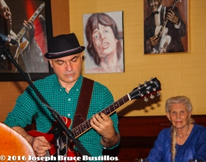 2016-01-08 Oak Hill Drifters at Smiling Bison: George Dimitrov works his guitar while a fan looks on